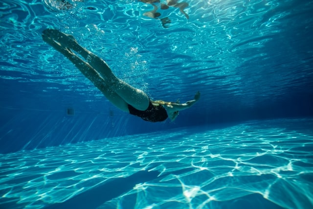 プールで潜っている女性