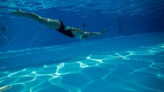 プールに潜り込む女性