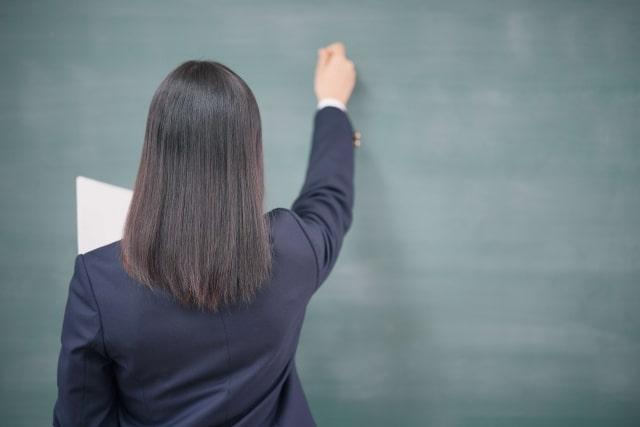 黒板に文字を書く女子高生