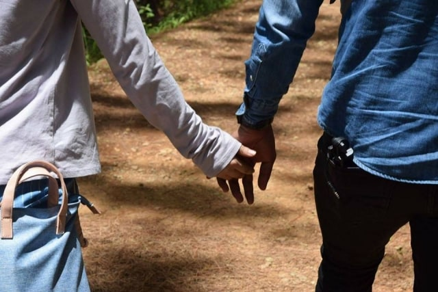 手をつないで歩いている男女